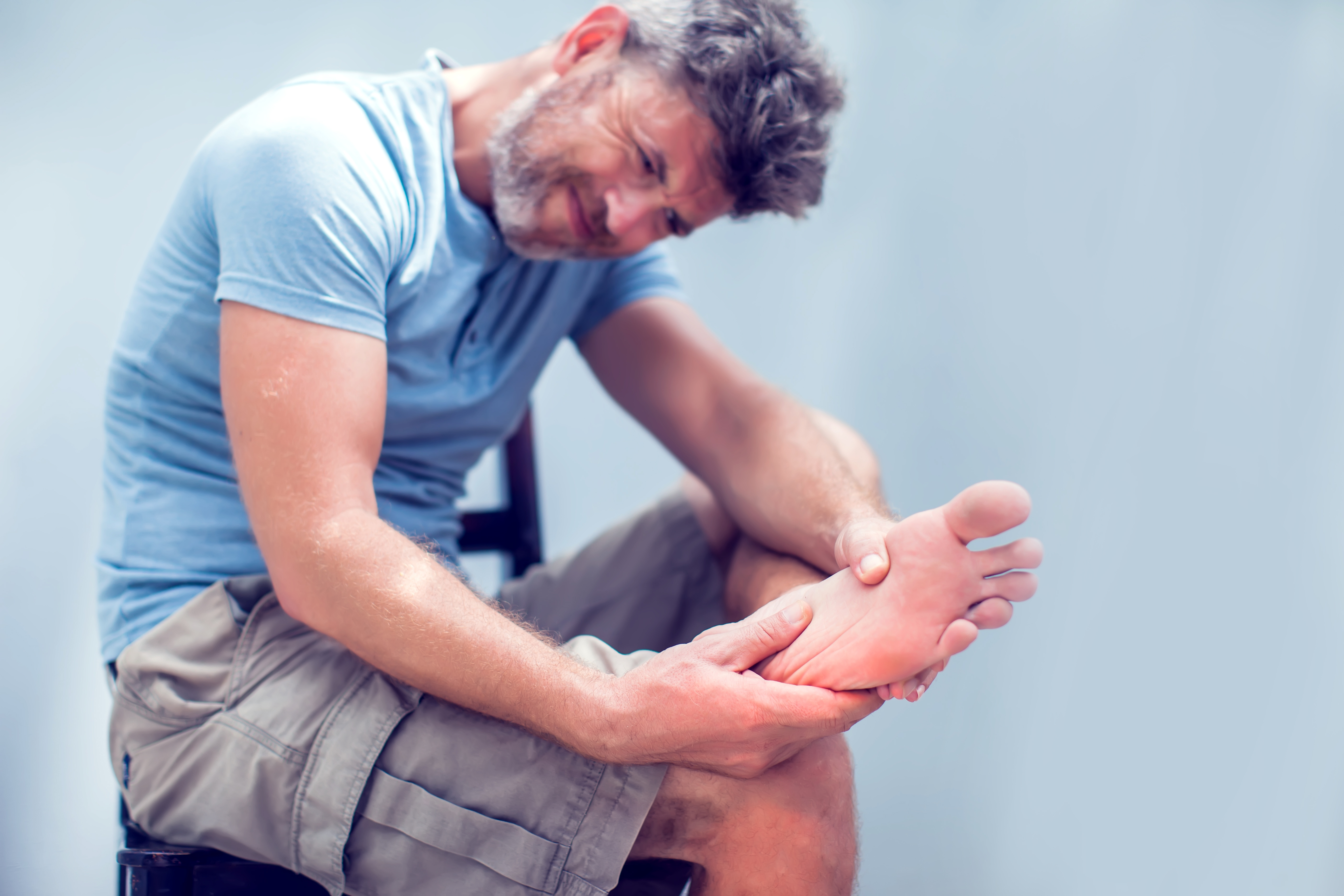 AdobeStock 212216478 - Man hand holding foot with pain, health care and medical concept